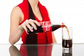 NAKHODKA, RUSSIA - JANUARY 18, 2014: Asian girl pours a Coca-Cola from a bottle into a glass. Coca-C