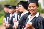 stock photo of graduation gown  - pretty african female college graduate at graduation with classmates - JPG