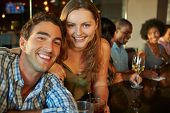 Couple Enjoying Drink At Bar With Friends