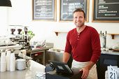 stock photo of apron  - Customer Paying In Coffee Shop Using Touchscreen - JPG