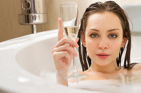 foto of douching  - A young beautiful  woman is enjoying a bath with a glasses of champagne - JPG