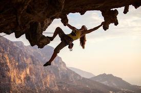 stock photo of rocking  - Rock climber at sunset - JPG