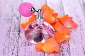 stock photo of perfume  - Perfume bottle with petals on table close - JPG