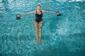 picture of day care center  - Fit blonde working out with foam dumbbells in swimming pool at the leisure centre - JPG