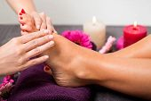 stock photo of therapist massage  - Woman having a pedicure treatment at a spa or beauty salon with the pedicurist massaging the soles of her feet with a pumice stone to cleanse dead skin and stimulate the tissue - JPG