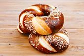 stock photo of pretzels  - hot mixed pretzels topped by sesame seeds over wooden table - JPG