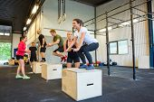 image of personal assistant  - Male and female athletes doing box jumps at gym - JPG