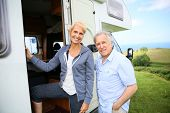 stock photo of camper  - Senior couple climbing camper door steps - JPG