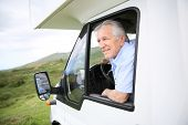 image of motorhome  - Senior man in motorhome sitting by steering wheel - JPG