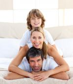 foto of little boy  - Little boy and his parents playing lying on the bed - JPG