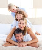 stock photo of family fun  - Happy family having fun in the bedroom - JPG