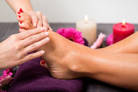 picture of stimulating  - Woman having a pedicure treatment at a spa or beauty salon with the pedicurist massaging the soles of her feet with a pumice stone to cleanse dead skin and stimulate the tissue - JPG
