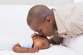 stock photo of babygro  - Adorable baby boy sleeping while being watched by father at home in the living room - JPG