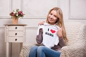 stock photo of expecting baby  - Portrait of young attractive happy Caucasian woman holding baby bodysuit sitting in the armchair - JPG