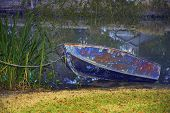 stock photo of bayou  - old rowboat with chipped paint tied up to the embankment - JPG