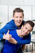 stock photo of piggyback ride  - Friendly brothers twins having fun riding piggyback in the white home or restaurant interior - JPG