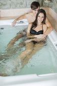 stock photo of hot-tub  - Young couple relaxing in the hot tub - JPG