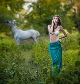 stock photo of beautiful horses  - Young women in a blue long skirt and white bra at sunset in forest with a white horse in background  - JPG