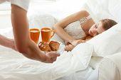 foto of bed breakfast  - Men brings breakfast to bed for his sleeping girlfriend - JPG