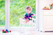 stock photo of daycare  - Cute curly little girl funny toddler wearing a warm colorful knitted dress reading a book relaxing in a white rocking chair next to a big garden view window at home or daycare center