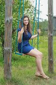 foto of swing  - Portrait of brunette girl in navy blue sundress is riding on handmade swing - JPG