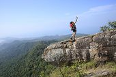 stock photo of cliffs  - woman hiker use digital tablet taking photo at mountain peak cliff - JPG