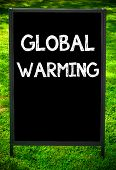 image of global-warming  - GLOBAL WARMING message on sidewalk blackboard sign against green grass background - JPG
