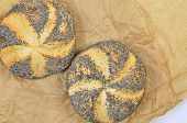 stock photo of baps  - close up of two poppy seed rolls on greaseproof paper - JPG