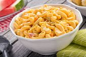 foto of watermelon  - A bowl of delicious creamy macaroni and cheese salad on a rustic picnic table with watermelon and corn - JPG