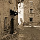 foto of italian alps  - Narrow street between old medieval stone buildings - JPG