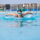 picture of blue butterfly  - Young girl in goggles and cap swimming butterfly stroke style in the blue water pool - JPG