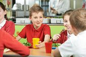 picture of pupils  - Group Of Pupils Sitting At Table In School Cafeteria Eating Meal - JPG