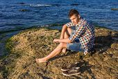image of nearly nude  - Attractive young fashion sexy man sitting on a rock near the sea water with shoes beside him - JPG