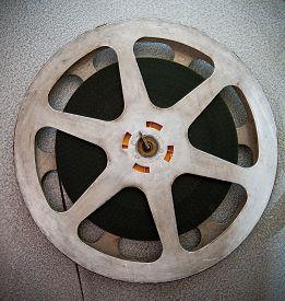 stock photo of mm  - Movie reels part with filmstrip crossing on projector detail 16 mm film format in vintage colors - JPG