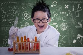 picture of mad scientist  - Mad little scientist doing experiment with chemical fluid and looking at camera - JPG
