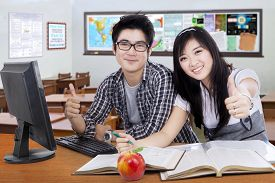 stock photo of indian apple  - Portrait of two attractive high school student smiling at the camera while studying and showing thumbs up in the classroom - JPG