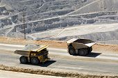 image of slag  - Two monster dump trucks pass each other in an open pit mine - JPG