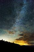Milky Way And Sky Full Of Stars Reaching Across The Night Sky, Light From Horizon Behind Treed Mount poster