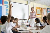 stock photo of 11 year old  - Student volunteering in class with teacher at board - JPG