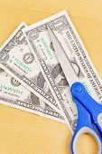 image of budge  - Scissors on Dollar Bills for Budge Cut Concept - JPG