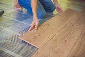 Man Installing New Wooden Laminate Flooring. Infrared Floor Heating System Under Laminate Floor poster