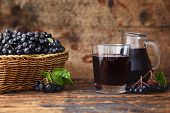 Fresh aronia berries and aronia berry juice in glasses poster