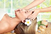 Beautiful blond woman lying down on massage table in spa salon, enjoying facial massage, doing facia poster