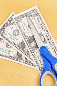image of budge  - Scissors on Dollar Bills for Budge Cut Concept - JPG