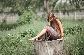 Dreaming Hippie Girl Sitting On A Big Stump In A City Park. poster