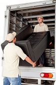 picture of shipping receiving  - Men working for a moving services company unloading a sofa from a truck - JPG