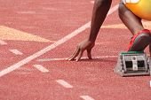 stock photo of race track  - A sprinter in a track and field race is poised at the starting line waiting for the start - JPG