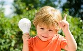 Little Cute School Boy And Electric Bulb. Smart Kid Having A Bright Idea. Holding Index Finger Up An poster