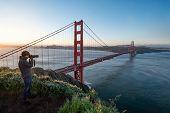 Asian Man Photographer And Tourist Enjoy Taking Photo Of Golden Gate Bridge During Sunrise, Iconic B poster
