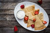 Crepes With Strawberry And Cream Sauce. Homemade Thin Crepes For Breakfast Or Dessert On Wooden Back poster